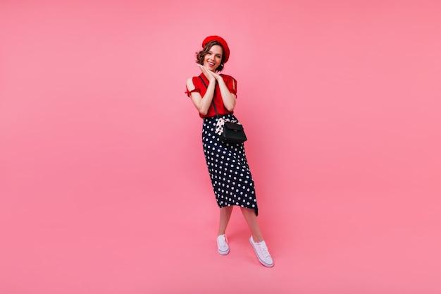 В полный рост портрет вдохновленной стройной девушки во французском наряде. фотография в помещении улыбающейся мечтательной женщины в длинной юбке.