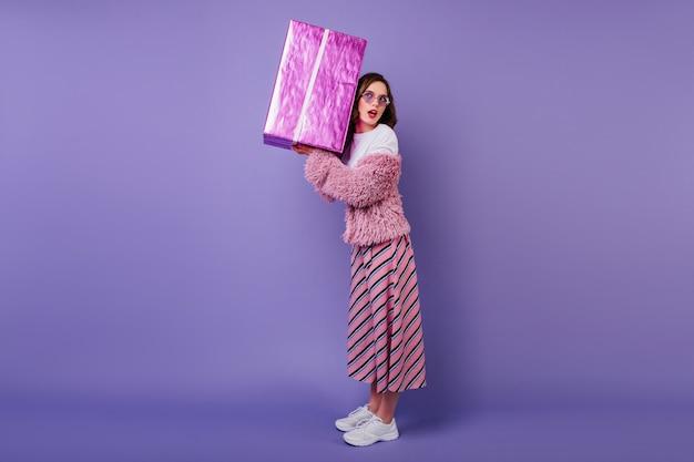 大きなプレゼントボックスを持っている白いスニーカーに興味のある女性の全身像。華やかな誕生日の女の子。