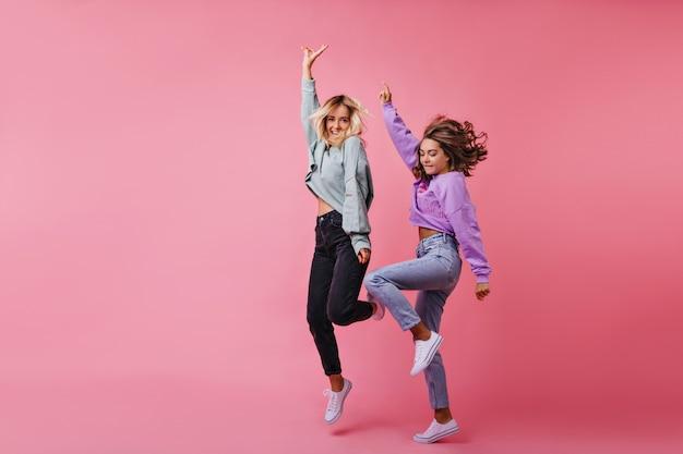 幸せな感情を表現するジャンプする白人の女の子の全身像。一緒に踊る面白い親友の肖像画。