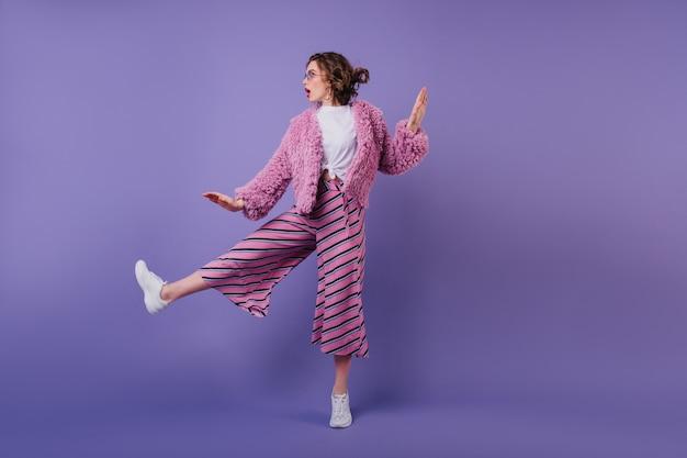 縞模様のズボンで踊る愛らしい巻き毛の女性の全身像。紫色の壁にジャンプするファッショナブルなブルネットの少女。