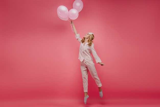 風船でつま先で立っている素敵なのんきな女の子の全身像。ピンクのパジャマと笑顔でジャンプするアイマスクの巻き毛の女性の屋内写真。