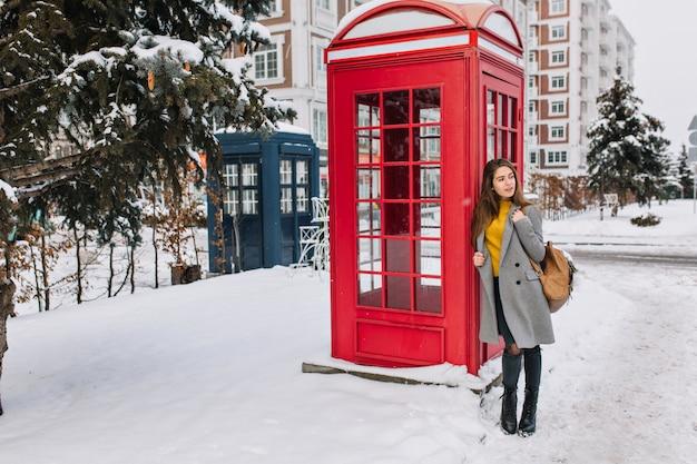 革のバッグが電話ボックスの近くに立って目をそらしている素敵なヨーロッパの女性の全身像。冬の日の電話ボックスの横にポーズグレーのコートを着た見事な白人女性の屋外写真。
