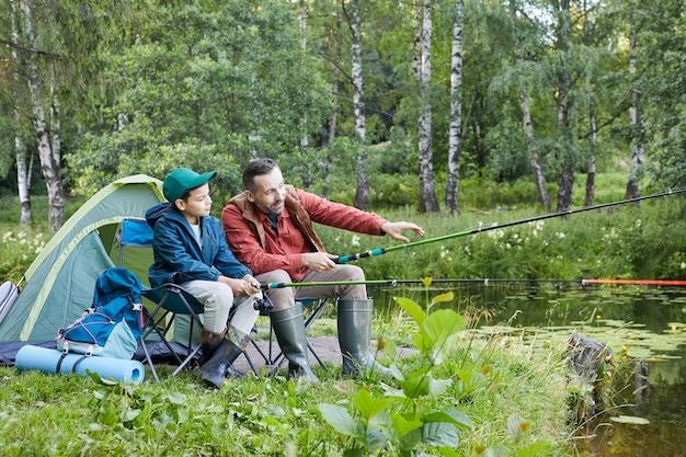 Портрет любящих отца и сына в полный рост вместе на рыбалке во время похода у озера, копия пространства