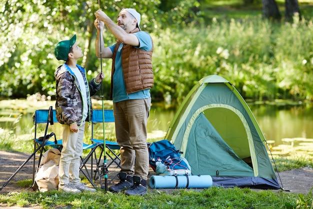 Портрет любящего отца в полный рост, учит сына настраивать рыболовное снаряжение, наслаждаясь вместе в походе, скопируйте пространство