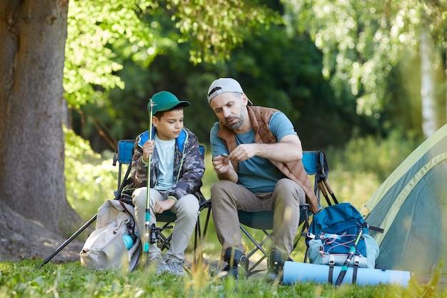Портрет любящего отца в полный рост, учит сына настраивать удочки, наслаждаясь вместе в походе, копия пространства