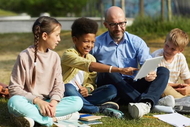 緑の芝生に座って、日光の下で屋外のクラスを楽しんでいる間、子供たちのグループと話している男性教師の全身像