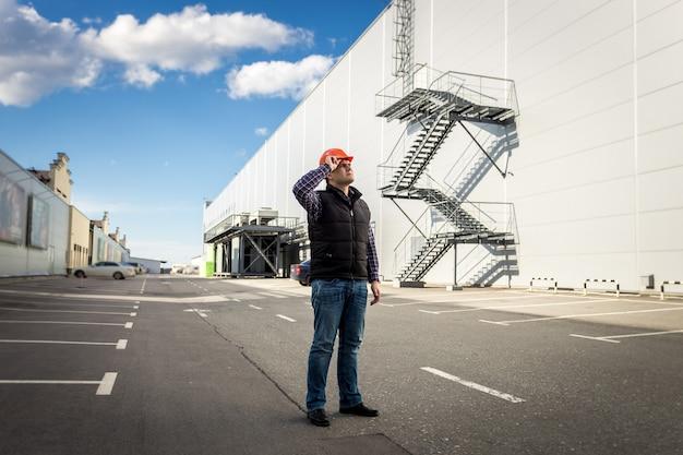 산업 건물의 주차장에 포즈를 취하는 남성 노동자의 전체 길이 초상화