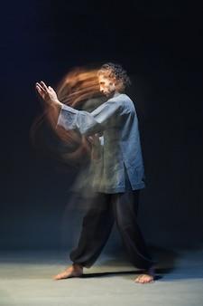 Полноразмерный портрет мужчины в кимоно, занимающегося боевыми искусствами, на черном фоне с мультиэкспозицией