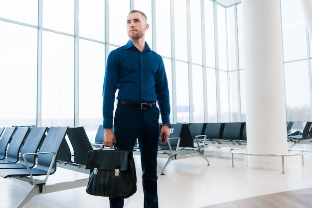 Полнометражный портрет человека ждать его полет в авиапорте. он доволен своей командировкой