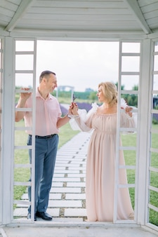 흰색 나무 전망대 밖에 서서 서로를 바라보고 꽃이 만발한 라벤더를 손에 들고 있는 성숙한 우아한 부부의 전체 길이 초상화