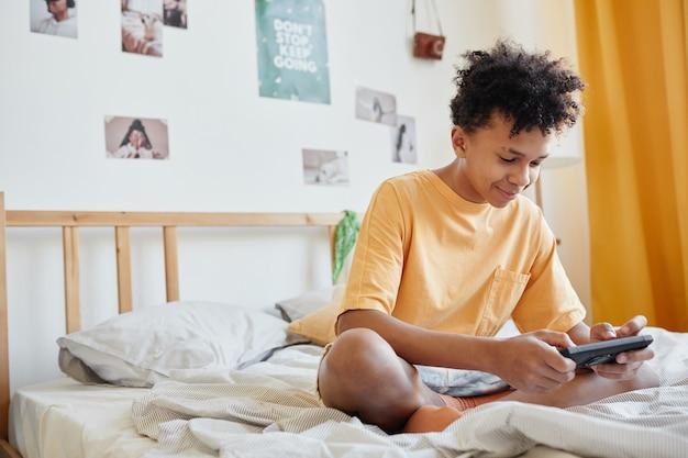 Портрет в полный рост мальчика-подростка смешанной расы, сидящего на кровати и играющего в мобильные игры через смартфон, копировальное пространство
