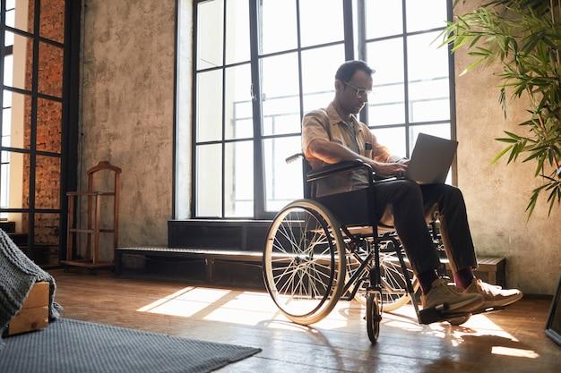 デザイナーのインテリア、コピースペースの窓のそばで自宅で作業しながらラップトップを使用して車椅子で現代の成人男性の完全な長さの肖像画
