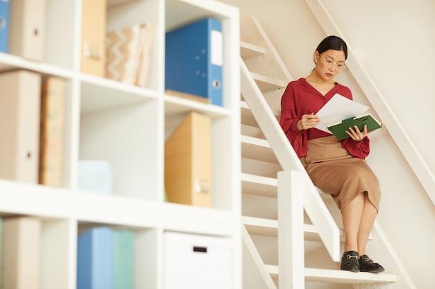 Портрет современной азиатской бизнес-леди в полный рост, сидя на лестнице в офисе и читая документы, копируя пространство