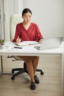 Полный портрет современной азиатской бизнес-леди, работающей за столом в белом офисе, копией пространства