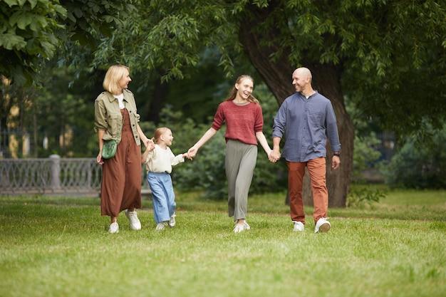 Портрет в полный рост современной беззаботной семьи с двумя детьми, держась за руки во время прогулки по зеленой траве на открытом воздухе