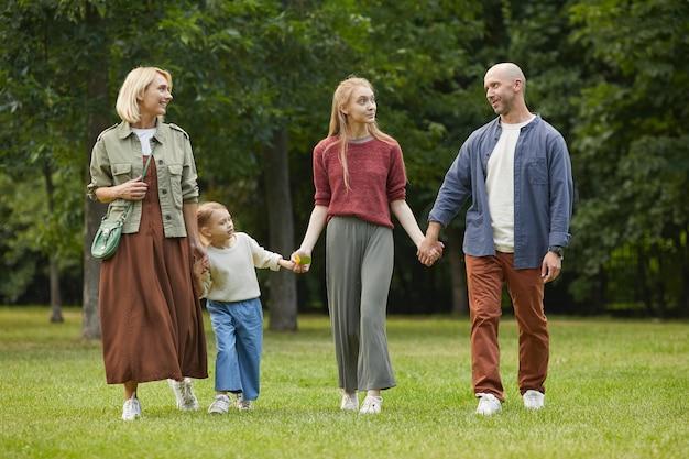 Портрет в полный рост современной семьи с двумя детьми, держась за руки во время прогулки по зеленой траве на открытом воздухе