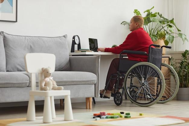 Полнометражный портрет современной женщины смешанной расы, использующей инвалидную коляску во время работы из дома за столом с детскими игрушками на переднем плане, копией пространства