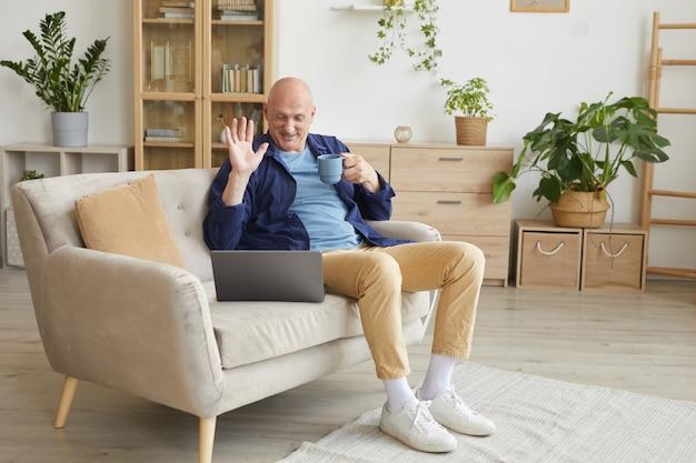 ノートパソコンのカメラで手を振って、自宅でビデオ通話中に幸せに笑っている現代の年配の男性の全身像