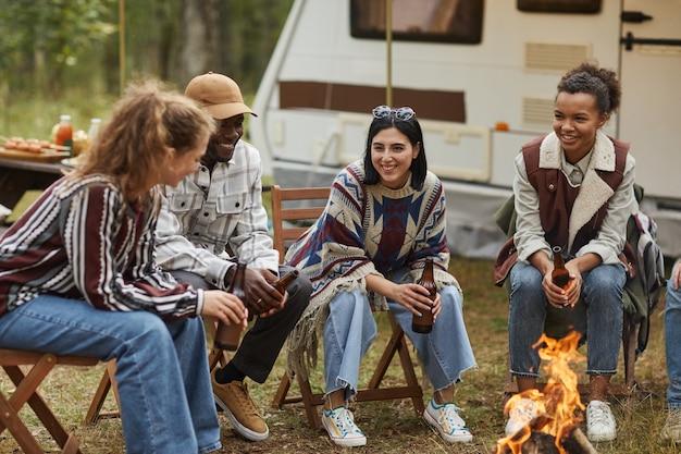 屋外でキャンプを楽しんだり、ビールを飲みながら火のそばに座って楽しんでいる現代の若者の全身像