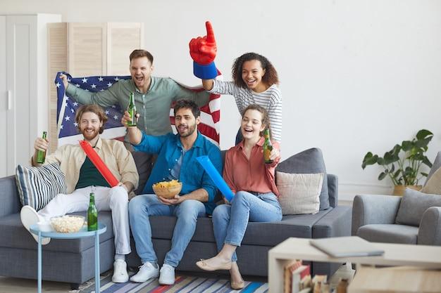 Портрет многонациональной группы друзей в полный рост, смотрящий спортивный матч по телевизору и эмоционально аплодирующий, держа в руках американский флаг