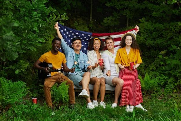 Портрет в полный рост многонациональной группы людей, держащих американский флаг, сидя на скамейке в лесу и наслаждаясь летними каникулами