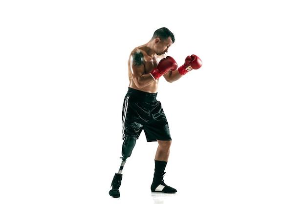 Портрет в полный рост мускулистого спортсмена с протезом ноги, копией пространства. боксер в красных перчатках. изолированный выстрел на белой стене.