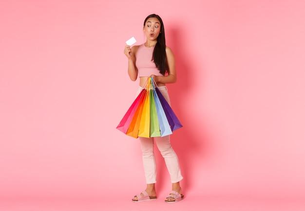 Полный портрет возбужденной симпатичной азиатской девушки в модной одежде, держащей хозяйственные сумки и кредит, дисконтной карты с довольной улыбкой, стоящей розовой стене, наслаждающейся выходными в торговых центрах.