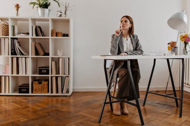 최소한의 사무실에 앉아 유행 복장에 잠겨있는 비즈니스 여자의 전신 초상화.