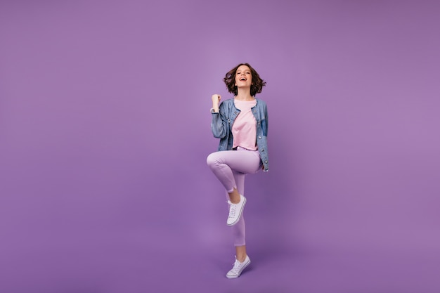 白い靴を履いて喜んでいる素晴らしい女性の全身像。白人の女の子はカジュアルな服を着て踊っています。
