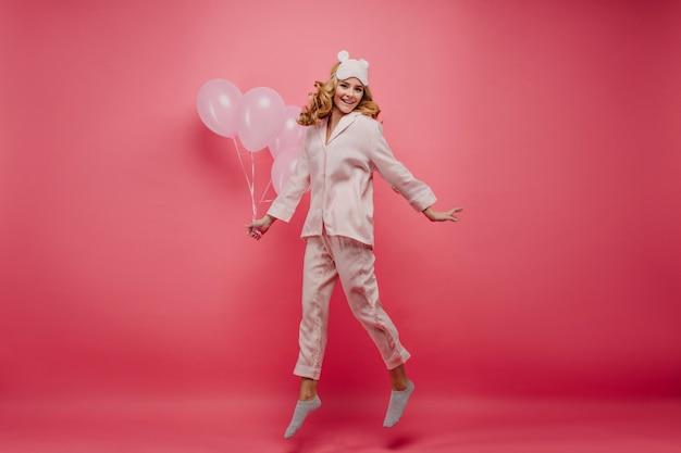 パーティーの後にリラックスして喜んでいる金髪の女性の全身像。ピンクの壁にエネルギーを表現するポジティブな誕生日の女の子の屋内写真。