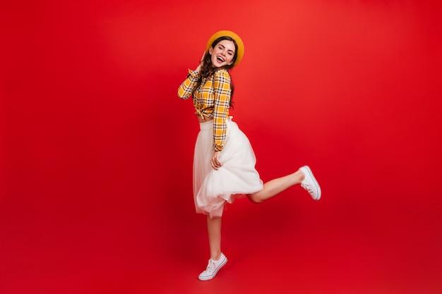 赤い壁にジャンプするポジティブでスタイリッシュな女性の全身像。格子縞のシャツと白いスカートの女性は素晴らしい気分で踊っています。