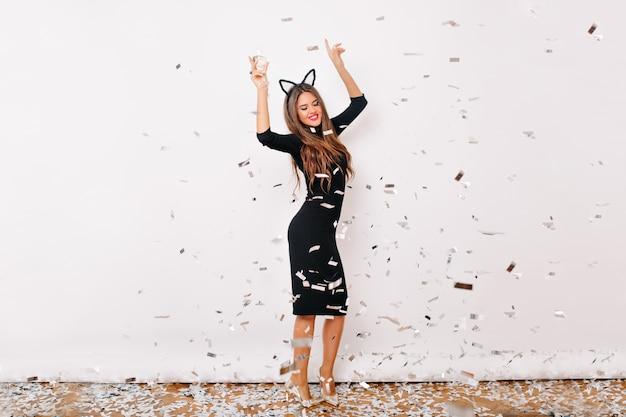 Портрет позитивной стильной женщины в полный рост, танцующей на дне рождения