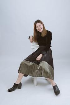 椅子に座っているかなりアジアビジネスの女性の完全な長さの肖像画