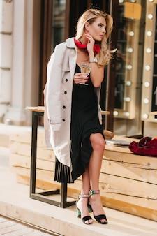 ワインのグラスとレストランの横に座って、天気の良い日を楽しんでいるきれいな金髪の女性の全身像。一人でシャンパンを飲む黒のドレスを着た女の子の屋外写真。