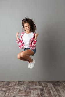Полнометражный портрет красивой прыгающей женщины в повседневной одежде