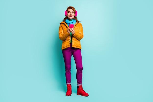 예쁜 아가씨의 전체 길이 초상화는 새 게시물 블로그를 작성하는 전화를 사용하여 트렌디 한 캐주얼 노란색 외투 스카프 보라색 바지 신발을 착용하십시오.