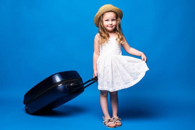 파란색 벽에 고립 된 수하물 예쁜 꼬마 소녀의 전체 길이 초상화. 주말 휴가에 해외로 여행하는 승객. 항공 비행 여행 개념.