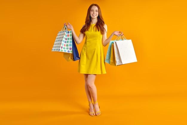 かわいいモデルの女性の全身像は、カメラの笑顔でポーズをとって黄色の背景に分離されたトレンディな黄色のドレスとハイヒールの靴を身に着けている海外販売ショッピングを楽しんでいる多くのパックを運ぶ