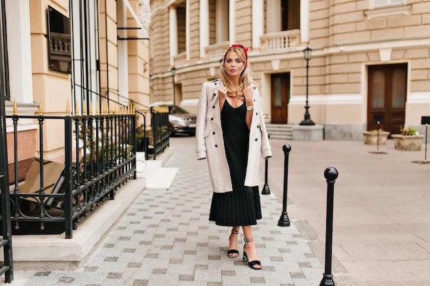 美しい建物の前で足を組んで立っているヴィンテージのドレスを着たきれいな女性の全身像。薄茶色のコートと流行の靴を履いている魅力的なブロンドの女の子の屋外の写真。