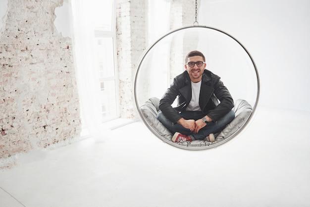 ぶら下がっている椅子の弾丸にカジュアルな座っていると白で分離されたカメラに笑顔でリラックスした流行に敏感な男の全身像》