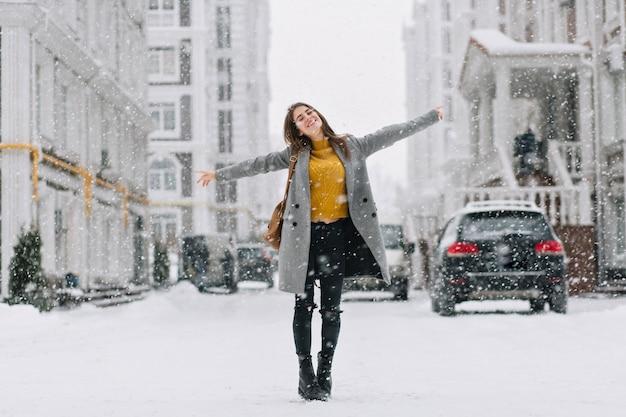 ロマンチックなヨーロッパの女性の全身像は、雪の日に長いコートを着ています。冬の街で自由な時間を楽しんでいる触発されたブルネットの女性の屋外の写真。
