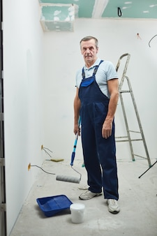 Портрет старшего строителя в полный рост, держащего валик и смотрящего в камеру во время ремонта дома, копией пространства