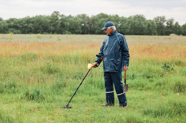 緑の牧草地で金属探知機とシャベルを使ってコインやアーティファクトを探すシニア男性の全身像
