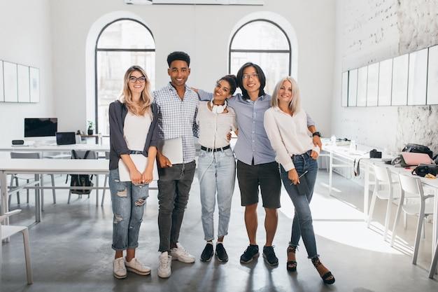 Полнометражный портрет застенчивой блондинки в белых кроссовках, держащей ноутбук после семинара и стоящей рядом с африканским другом. взволнованные иностранные студенты позируют вместе после лекции в просторном зале.
