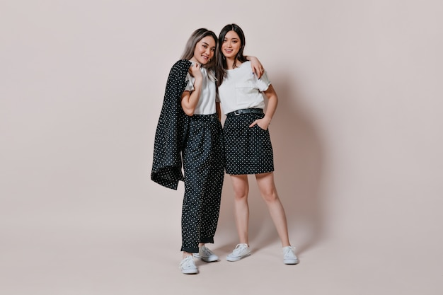 Портрет сестер в одинаковых нарядах в горошек в полный рост, позирующих на фоне изолированной стены