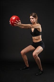 Полный портрет тощей кавказской женщины в спортивной одежде, делающей приседания с фитнес-мячом во время тренировки в тренажерном зале, изолированном на черном фоне