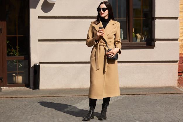 Полнометражный портрет стройной элегантной женщины носить бежевое пальто, черные сапоги, кожаную сумку и солнцезащитные очки, пить кофе на вынос, стоя на улице города. молодая красивая модель, глядя в сторону.