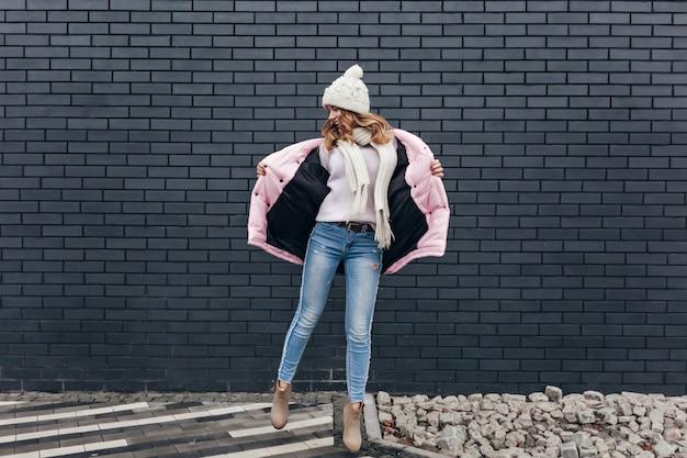通りで踊るジーンズとピンクのジャケットのスリムな女の子の全身像。ポジティブな感情を表現するニット帽のゴージャスな女性モデルの屋外ショット。