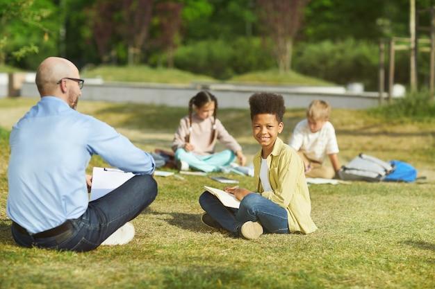 緑の芝生の上に座って、日光の下で屋外のクラスを楽しみながらカメラを見ている笑顔のアフリカ系アメリカ人の少年の全身像、コピースペース