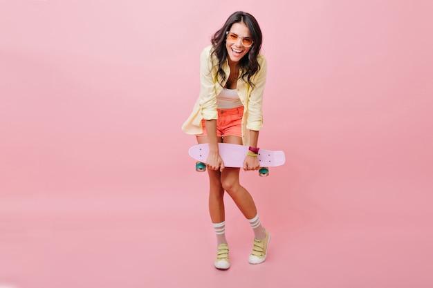 スケートボードを保持している黄色のジャケットで笑顔のブルネットの少女の全身像。明るいショートパンツとトレンディなサングラスのポーズで魅力的な若い女性。